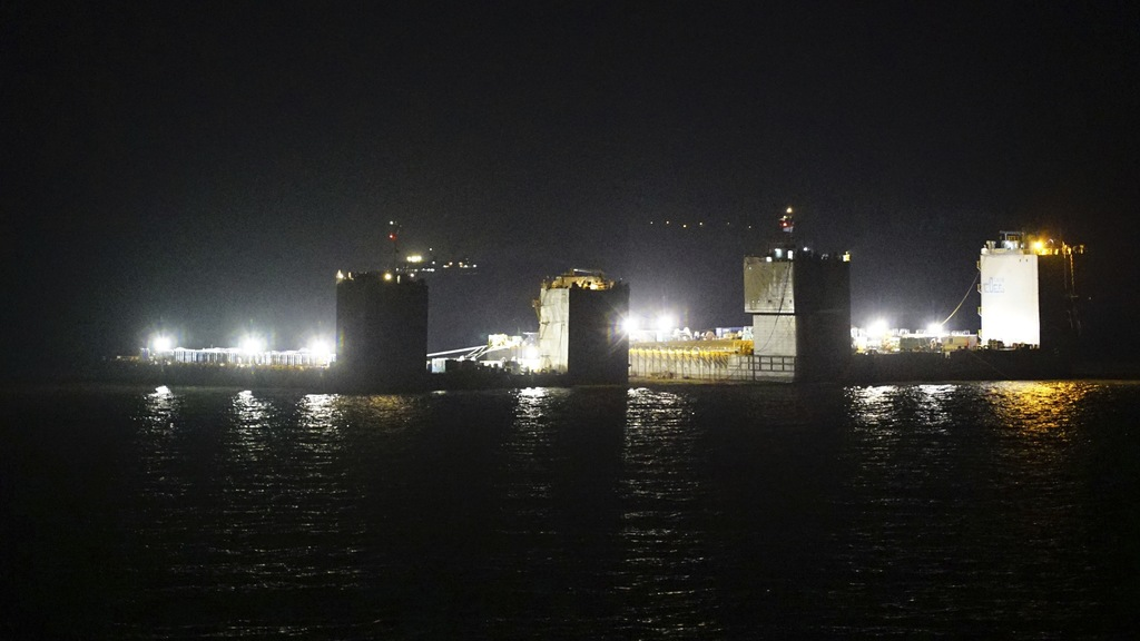 In this photo provided by South Korean Maritime Ministry, two barges attempt to salvage the sunken Sewol ferry in waters off Jindo, Sou...