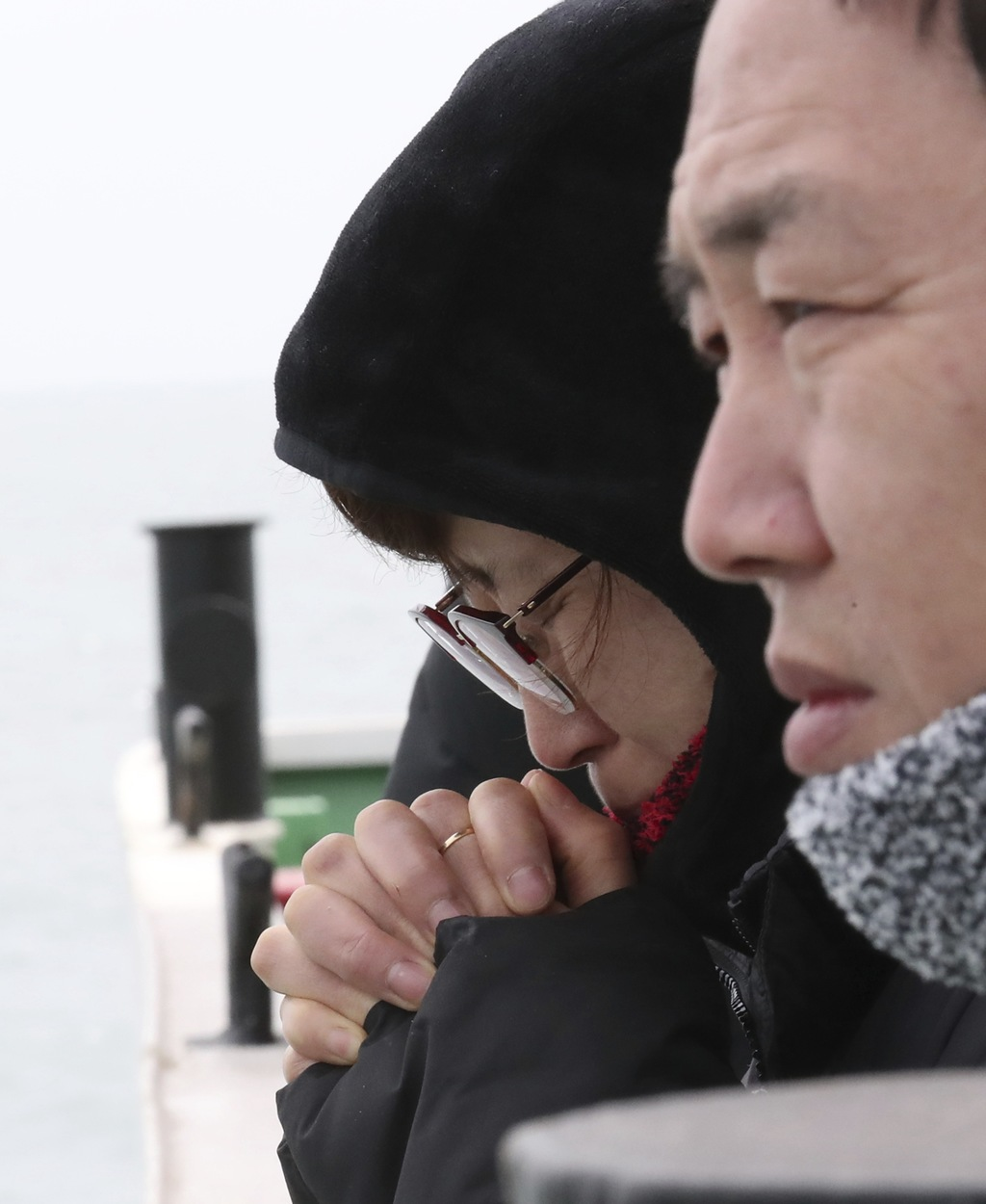 An unidentified relative of missing passengers of sunken Sewol ferry prays as two barges prepare to attempt to salvage the boat in wate...