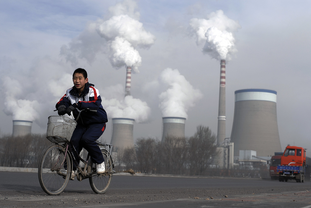 FILE - In this Dec. 3, 2009 file photo, a Chinese boy cycles past cooling towers of a coal-fired power plant in Dadong, Shanxi province...