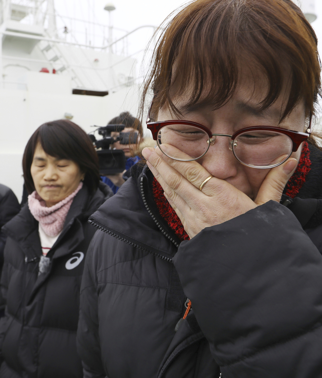 A relative of missing passengers of the sunken Sewol ferry cries as she watches workers lifting the boat in waters off Jindo, South Kor...