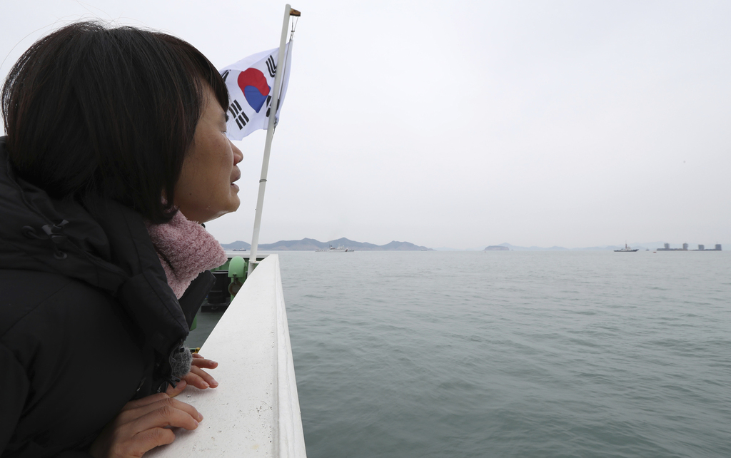 A relative of missing passengers of the sunken Sewol ferry weeps as she watches workers lifting the boat in waters off Jindo, South Kor...