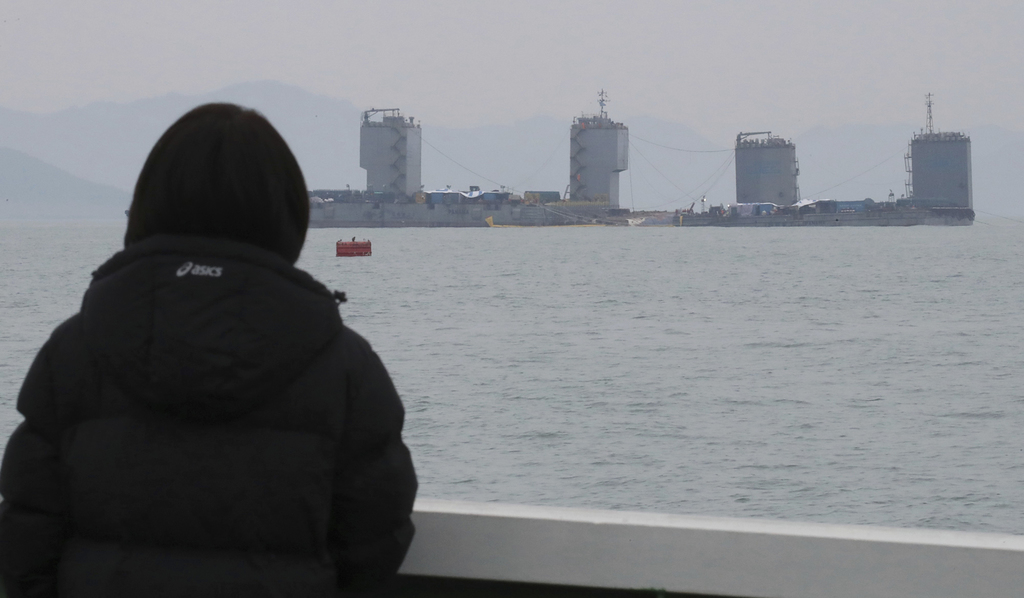 A relative of missing passengers of the sunken Sewol ferry watches workers lifting the boat in waters off Jindo, South Korea, Thursday,...