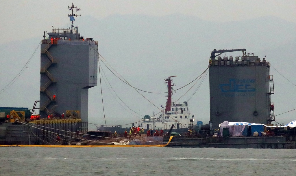 Workers prepare to lift the sunken Sewol ferry in waters off Jindo, South Korea, Thursday, March 23, 2017. South Korean workers on Thur...