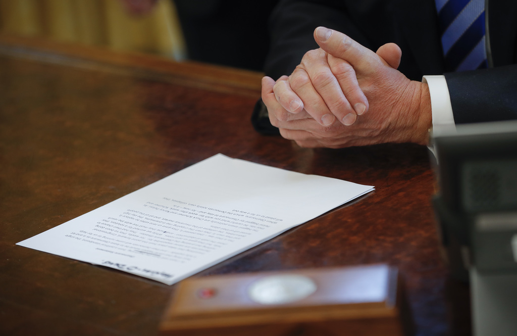 President Donald Trump reads from his prepared remarks while speaking about the health care overhaul bill, Friday, March 24, 2017, in t...