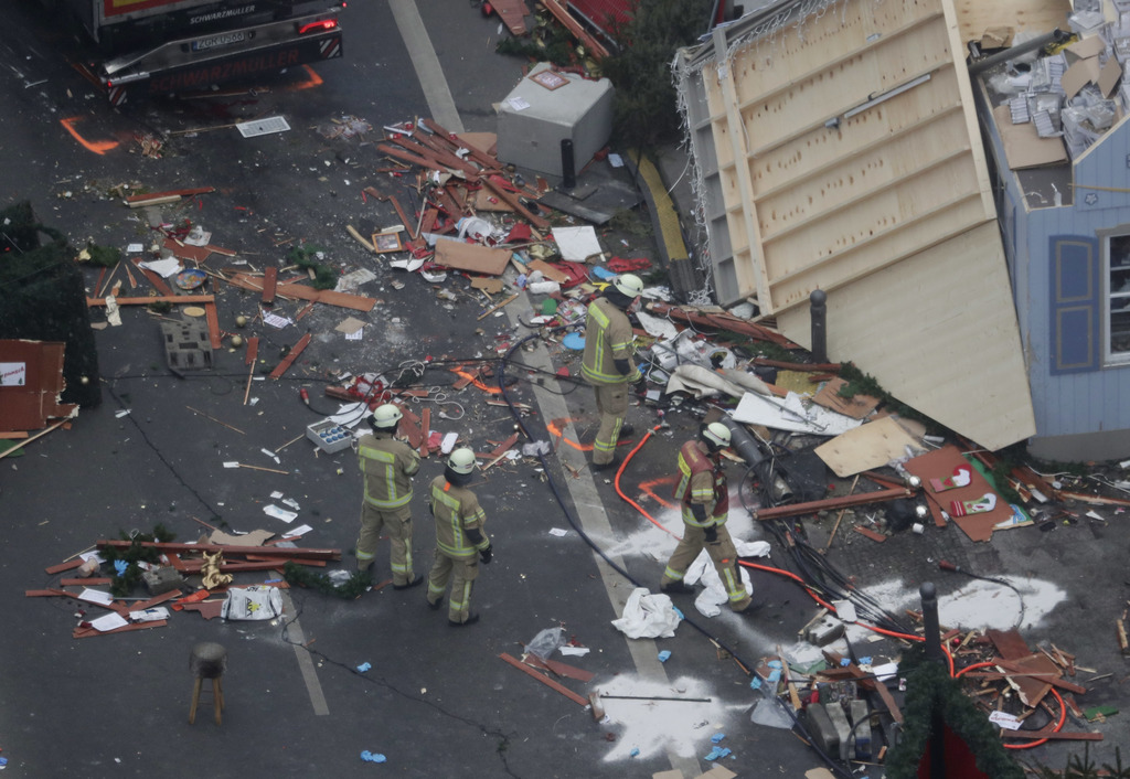 FILE - In this Dec. 20, 2016 file photo, German firefighters look at the debris after a truck attack on a Christmas market in Berlin th...