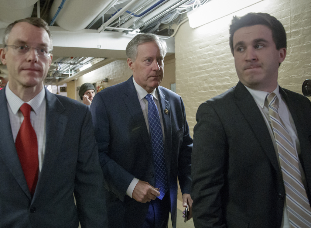 House Freedom Caucus Chairman Rep. Mark Meadows, R-N.C., center, rushes to a caucus in the basement of the Capitol in Washington, Frida...