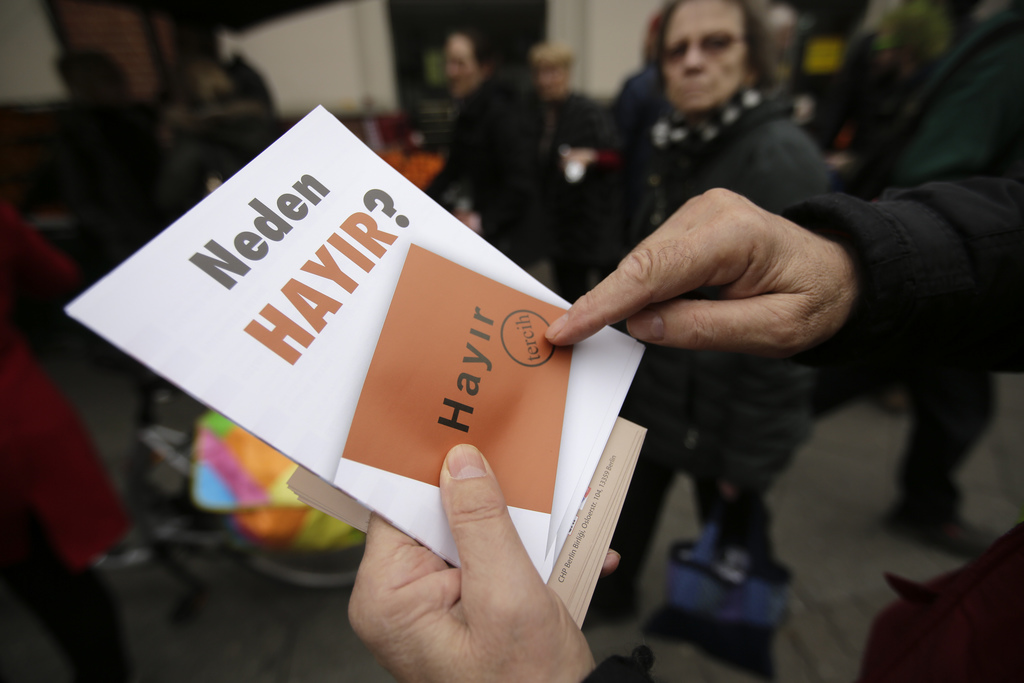 FILE - In this Tuesday, March 21, 2017 photo, a man hands out flyers, reading 'Why No' against the upcoming referendum in Turkey at the...