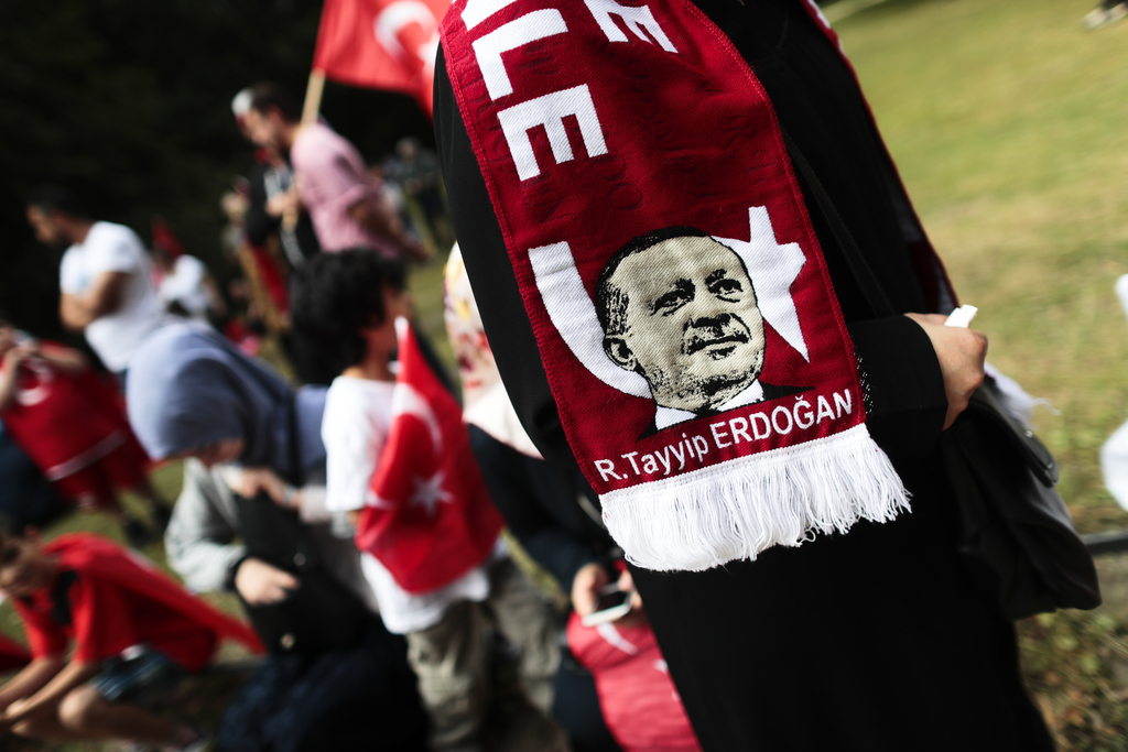 FILE - In this Saturday, July 16, 2016 file photo, a woman wears a scarf with a portrait of Turkish President Recep Tayyip Erdogan as s...