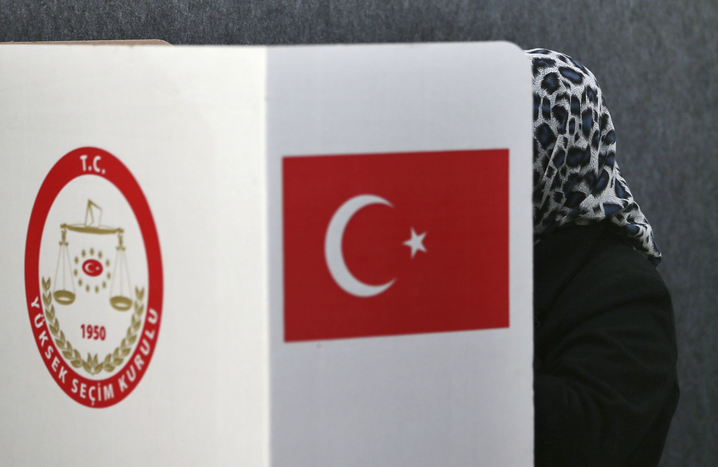 A woman casts her ballot for the referendum on the Turkish constitutional reform in the Turkish consulate in Huerth near Cologne, Germa...