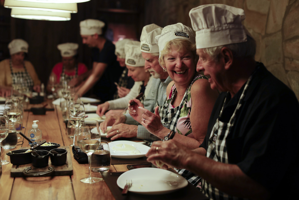 "In this March 20, 2017 photo Jane Andrews, from U.S, second left, smiles during an activity called ""The Argentine Experience"" in Buenos..."