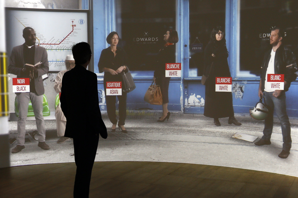 A visitor looks at a screen during a press visit of a prescient exhibit exploring the psychology behind racism at Paris' Museum of Mank...
