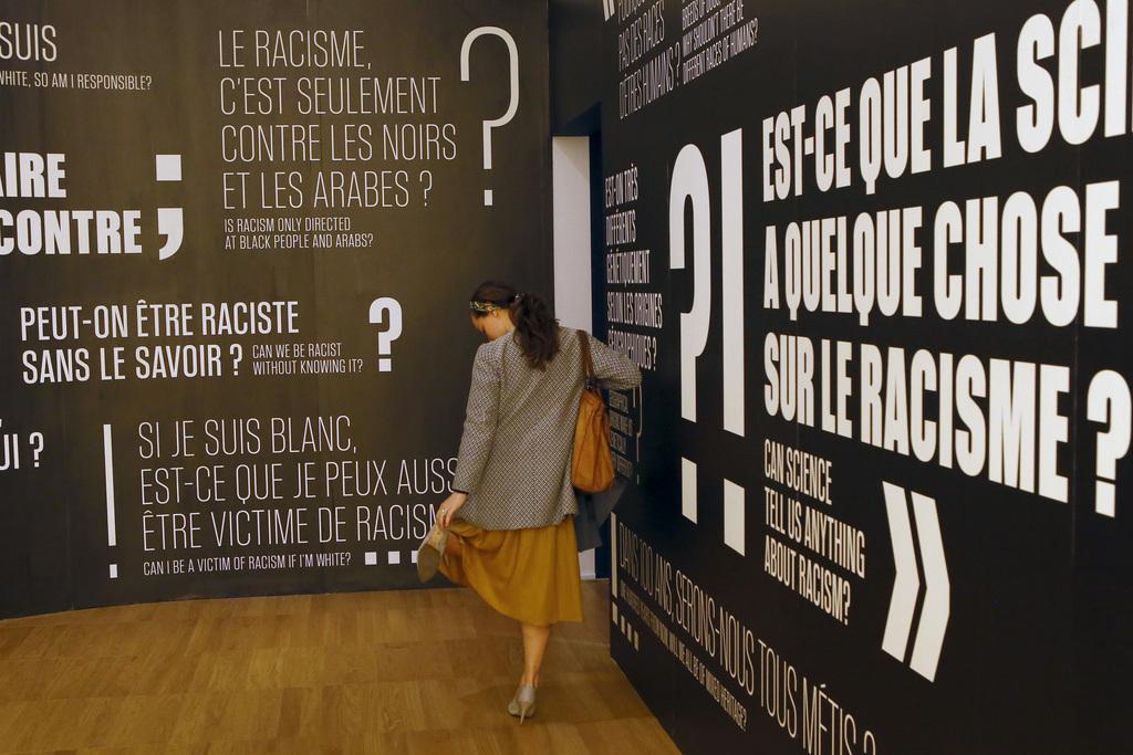 A visitor adjusts her escarpin during a press visit of a prescient exhibit exploring the psychology behind racism at Paris' Museum of M...