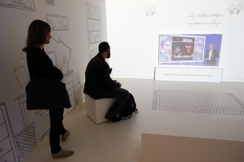 Visitors looks at a video screen during a press visit of a prescient exhibit exploring the psychology behind racism at Paris' Museum of...