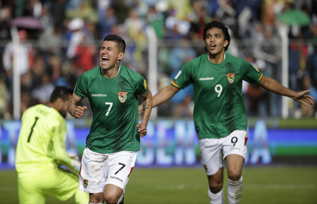 In this March 28, 2017 photo, Bolivia's Juan Carlos Arce (7) celebrates scoring his side's first goal against Argentina followed by tea...