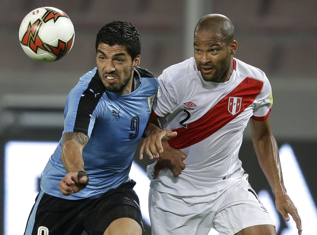 In this March 28, 2017 photo, Uruguay's Luis Suarez, left, fights for the ball with Peru's Alberto Rodriguez during a 2018 World Cup qu...