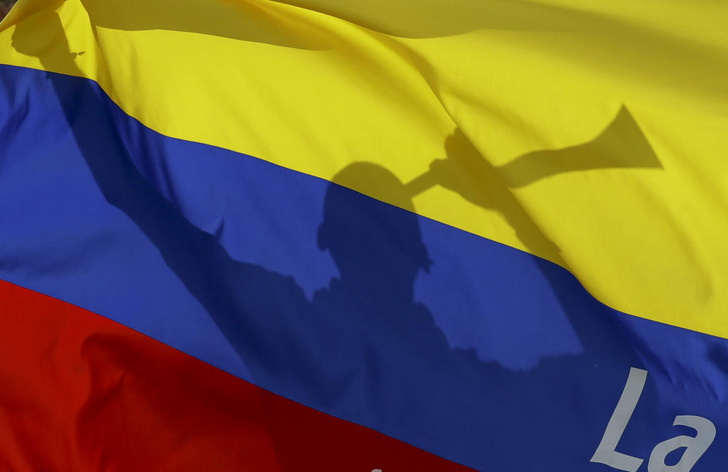 In this March 28, 2017 photo, a fan blows a horn behind a Colombian flag prior to 2018 World Cup qualifying soccer match between Colomb...