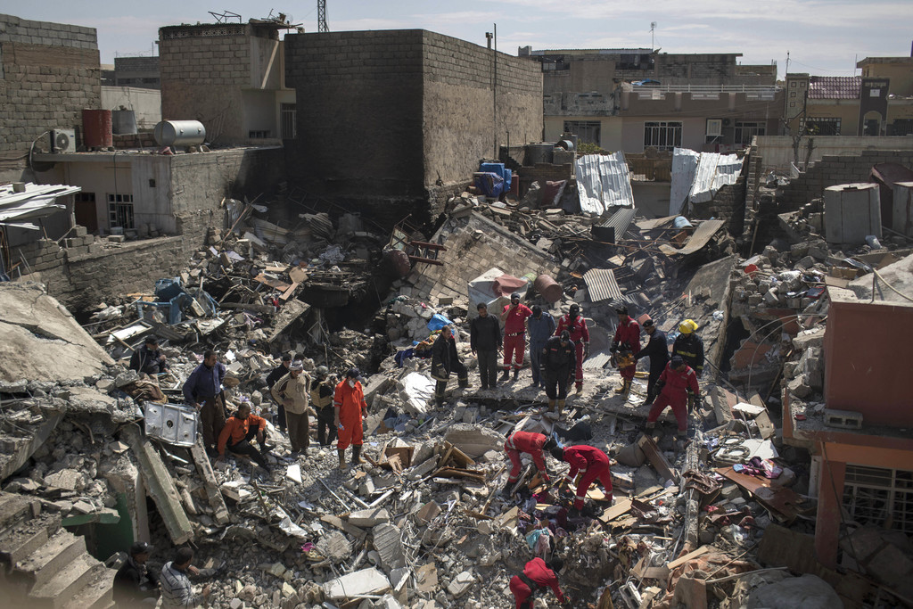 In this Friday, March 24, 2017 photo, civil protection rescue teams work on the debris of a destroyed house to recover the body of peop...