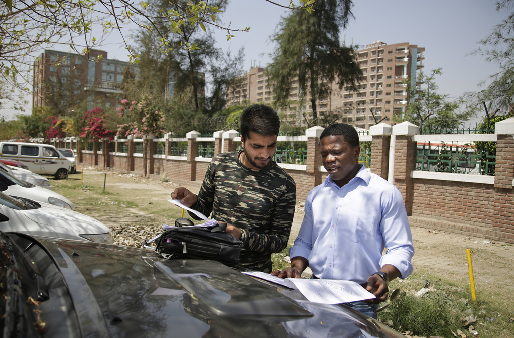 In this Thursday, March 30, 2017 photo, Congolese student Steve Katanga, right, and a Kashmiri student Amman Majid Bhat look at their n...
