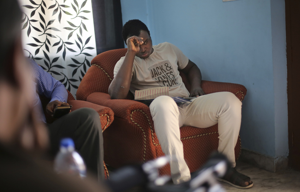 In this Friday, March 31, 2017 photo, Nigerian student Endurance Amalawa, 21, sits on a couch inside his apartment in Greater Noida, In...