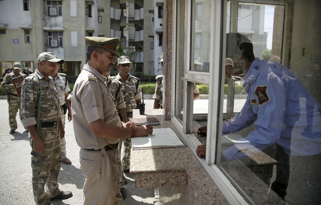 In this Thursday, March 30, 2017 photo, an Indian police officer writes instructions for a private security officer guarding a resident...