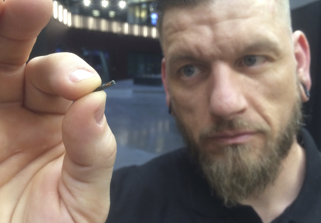 """Self-described """"body hacker"""" Jowan Osterlund from Biohax Sweden, holds a small microchip implant, similar to those implanted into worke..."""