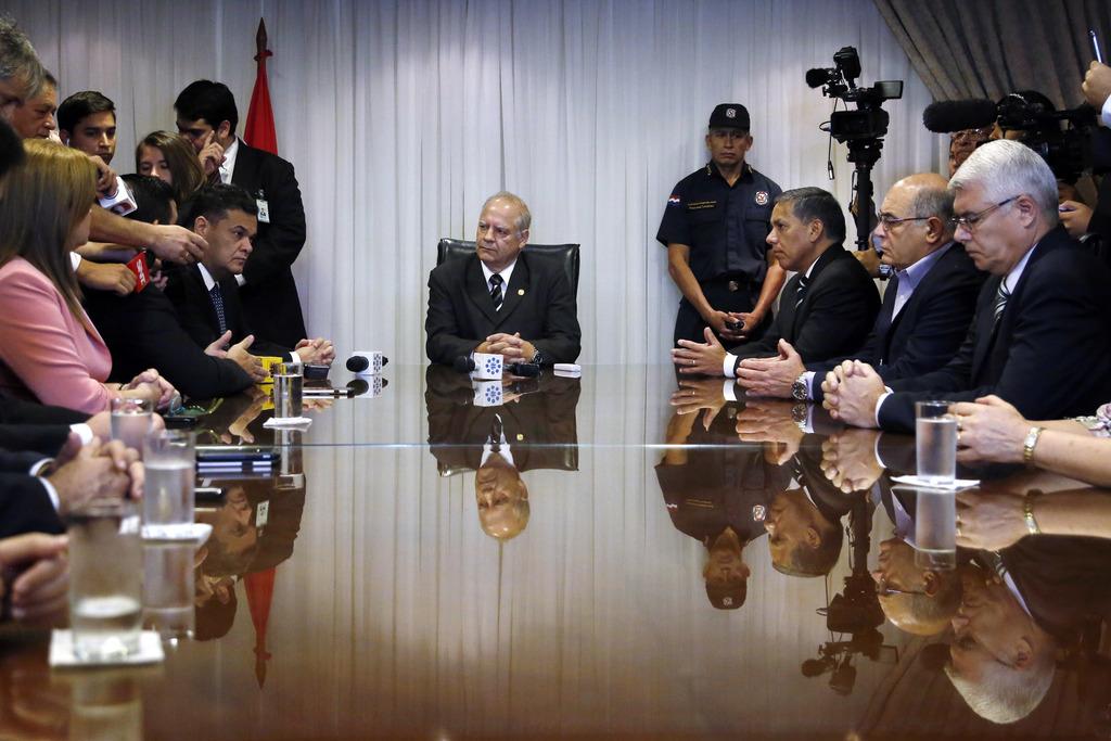 Paraguay's Supreme Court President Luis Benitez Riera, center, listens to Senate President Robert Acevedo during a meeting in Asuncion,