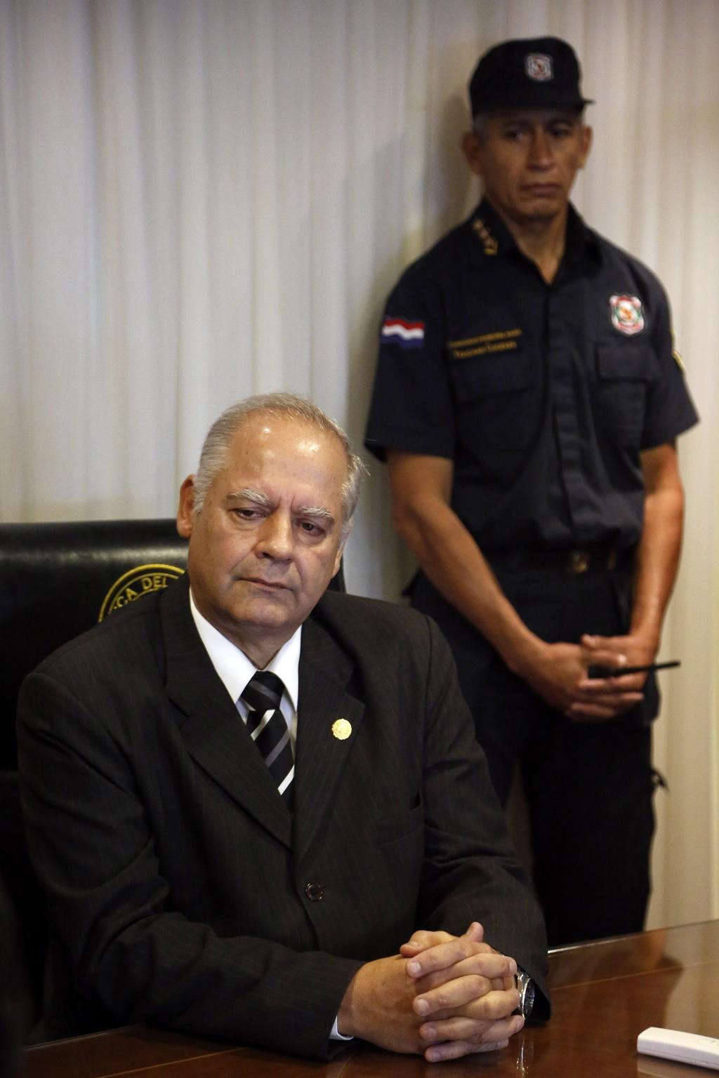 Paraguay's Supreme Court President Luis Benitez Riera listens to a senator during a meeting with Senate President Robert Acevedo in Asu