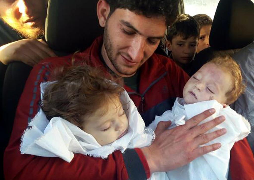 In this picture taken on Tuesday April 4, 2017, Abdul-Hamid Alyousef, 29, holds his twin babies who were killed during a suspected chem...