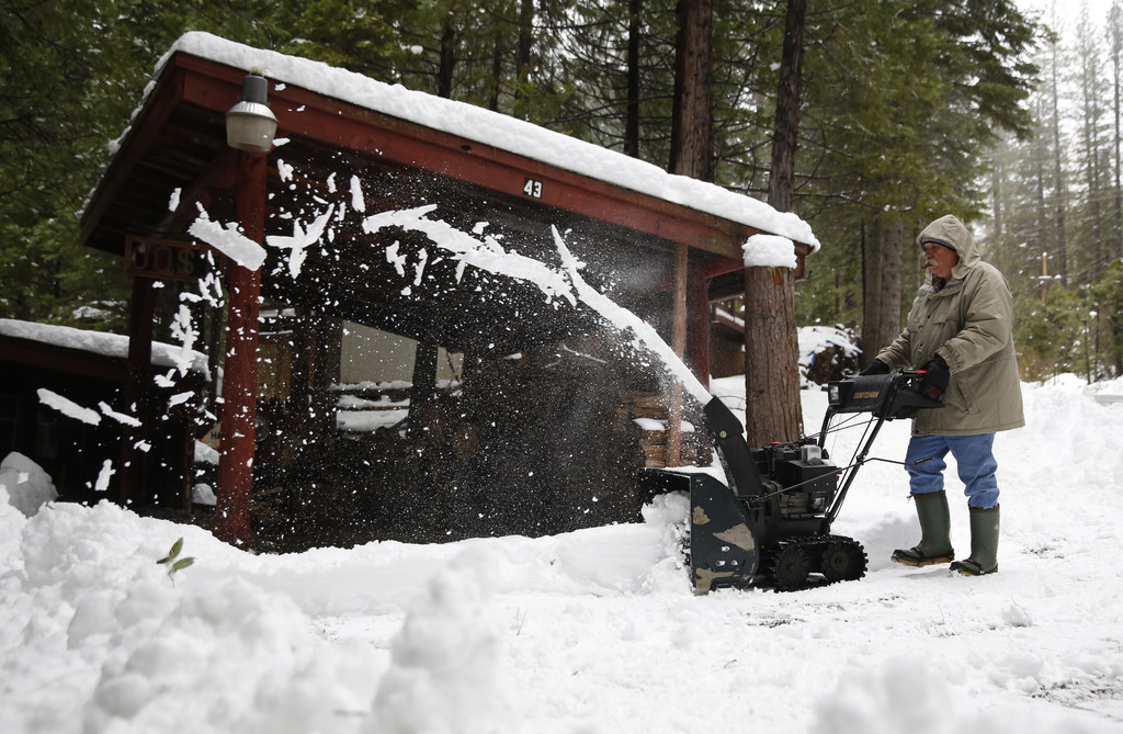 FILE - In this Jan. 3, 2017 file photo, Joe Johnson clears snow from a neighbor's driveway near Kyburz, Calif. Calif. Gov. Jerry Brown ...