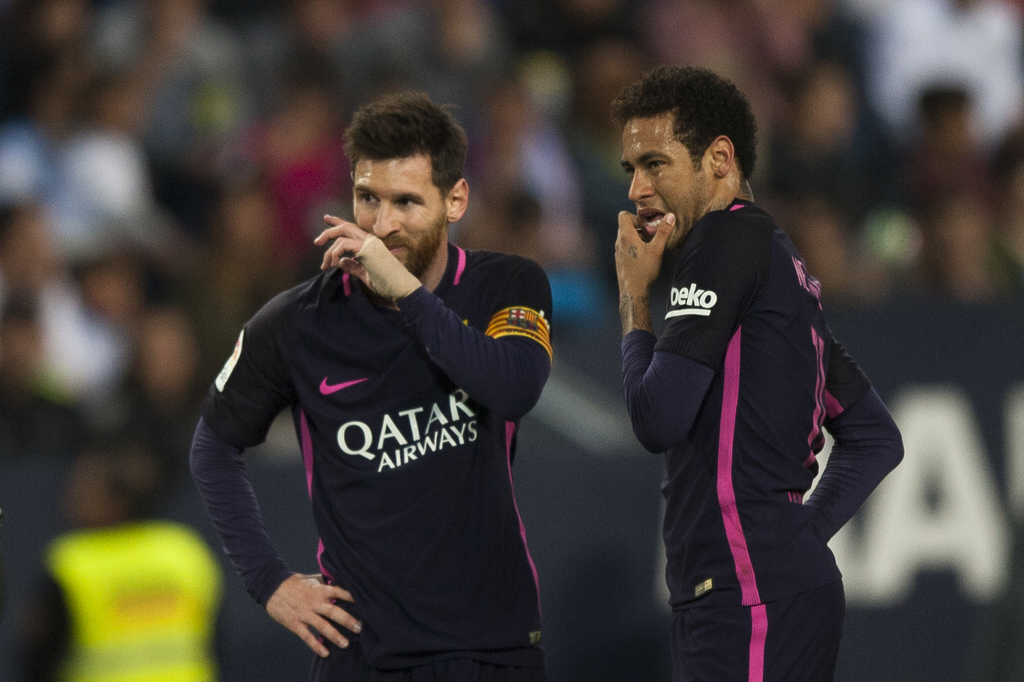 FC Barcelona's Lionel Messi, left, and Neymar da Silva from Brazil, right, gesture during their match against CF Malaga in a Spanish La...