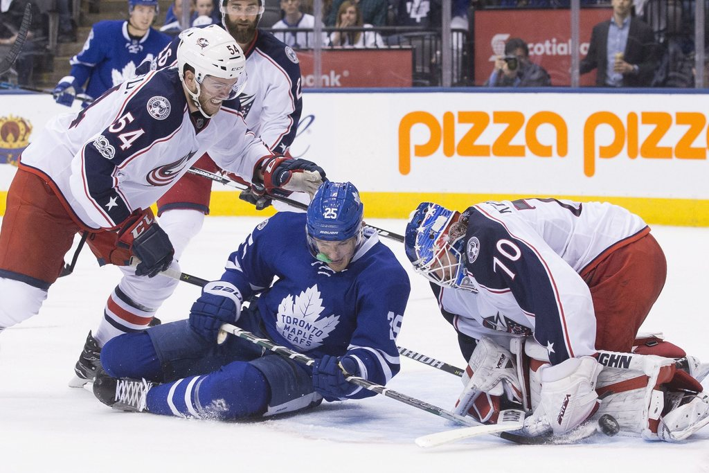 Columbus Blue Jackets goalie Joonas Korpisalo, right, makes a save on Toronto Maple Leafs' James van Riemsdyk, center, as Columbus Blue...