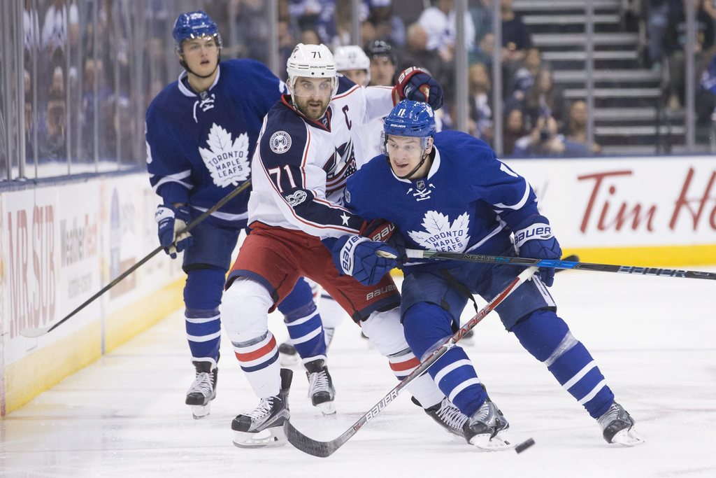 Toronto Maple Leafs' Zach Hyman, right, holds off Columbus Blue Jackets' Nick Foligno, centre, as Maple Leafs' William Nylander looks o...