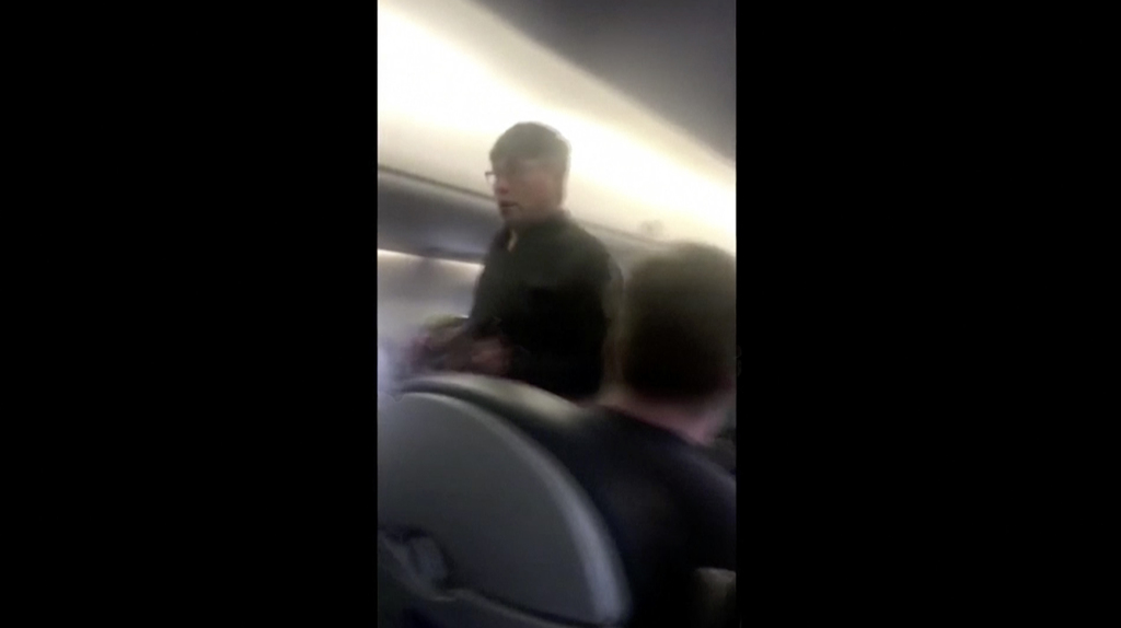This Sunday, April 9, 2017, image made from a video provided by Audra D. Bridges shows a passenger who was removed from a United Airlin...