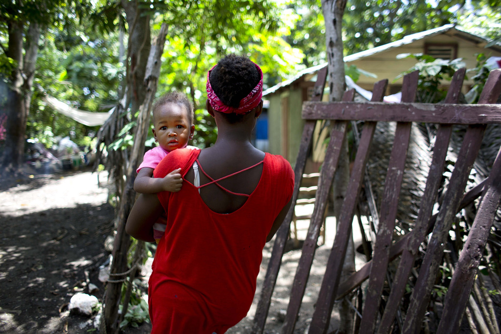In this Aug. 15, 2016 photo, Janila Jean, 18, carries her daughter as she walks to her friend's house before an interview in Jacmel, Ha...