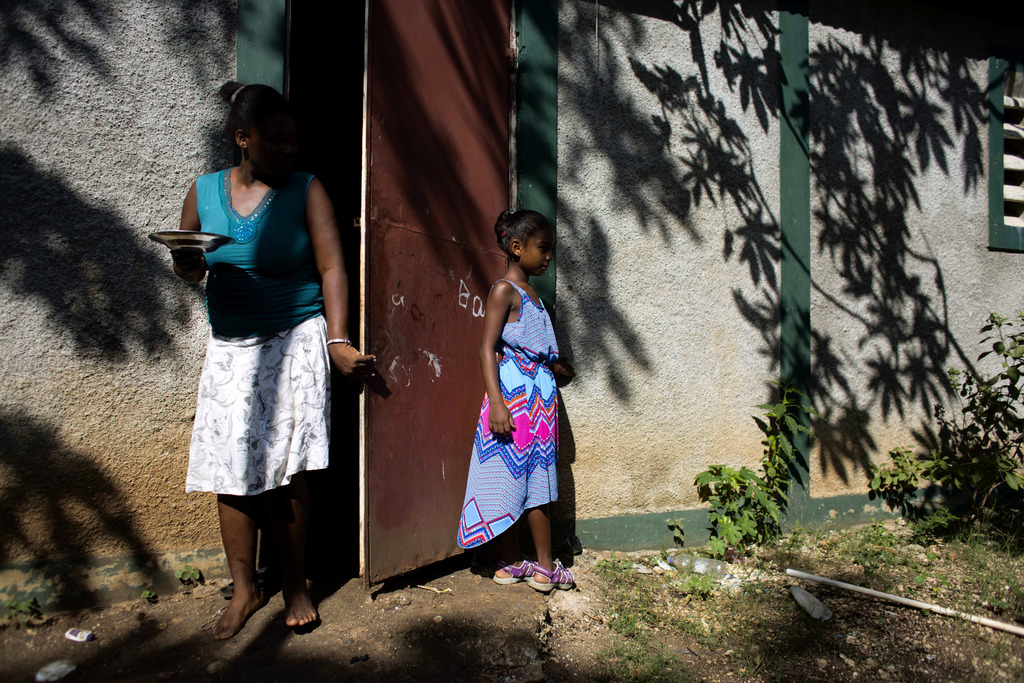 In this Aug. 17, 2016 photo, Marie-Ange Haitis, 40, stands with her daughter, Samantha, at their home in Leogane, Haiti. Haitis says sh...