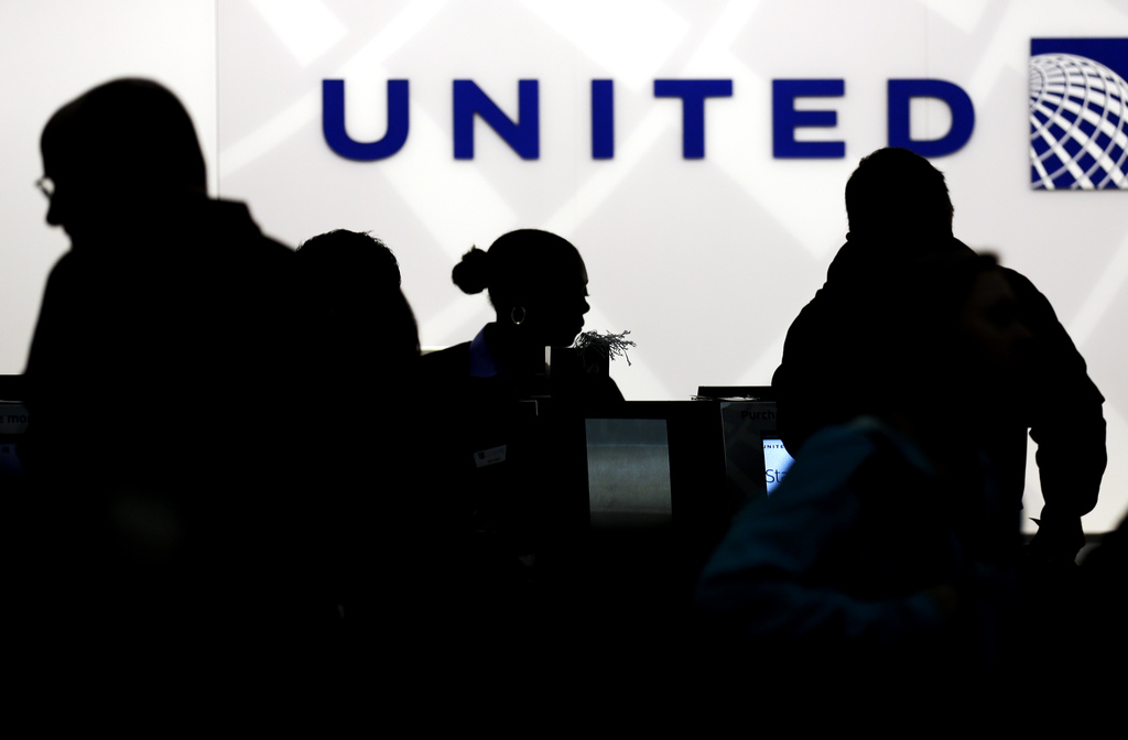 FILE - In this Saturday, Dec. 21, 2013, file photo, travelers check in at the United Airlines ticket counter at Terminal 1 in O'Hare In...