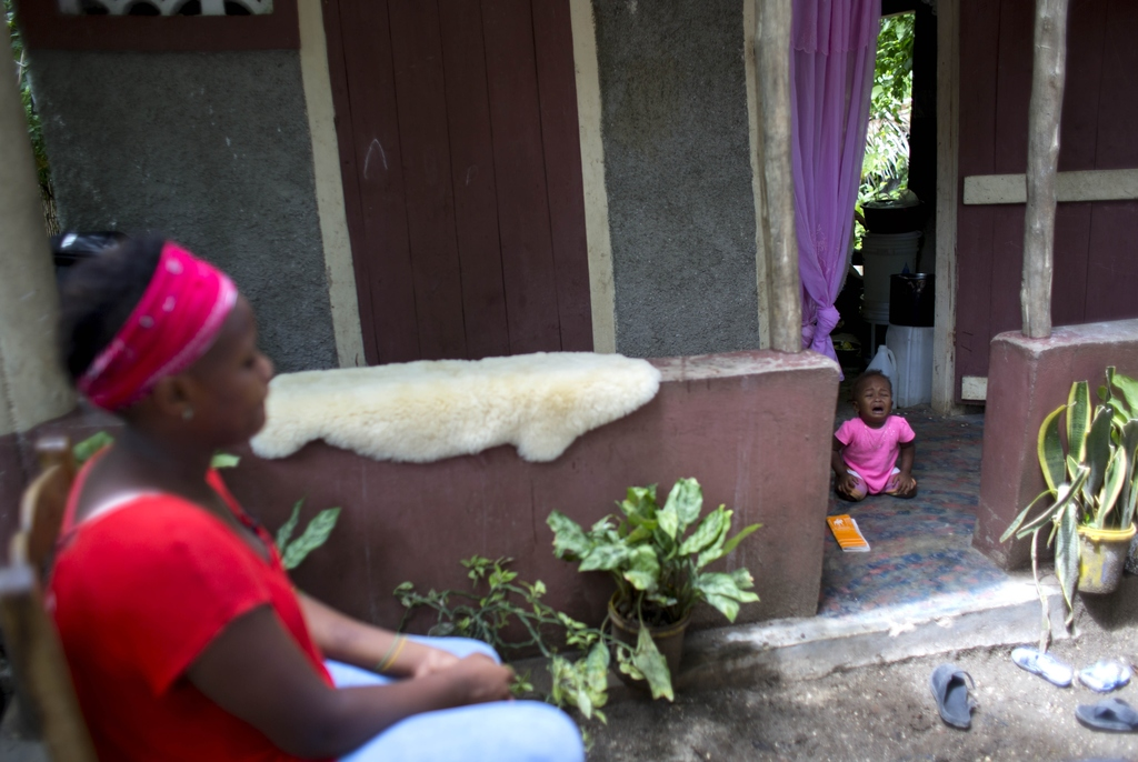 In this Aug. 15, 2016 photo, Janila Jean, 18, sits in front of a friend's house as her daughter cries during an interview in Jacmel, Ha...