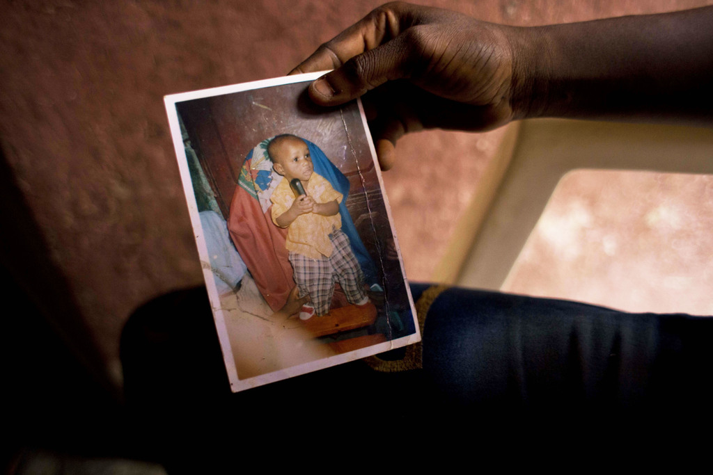 In this Aug. 11, 2016 photo, Martine Gestime 32, holds up a picture of her son, Ashford, during an interview in Port-au-Prince, Haiti. ...