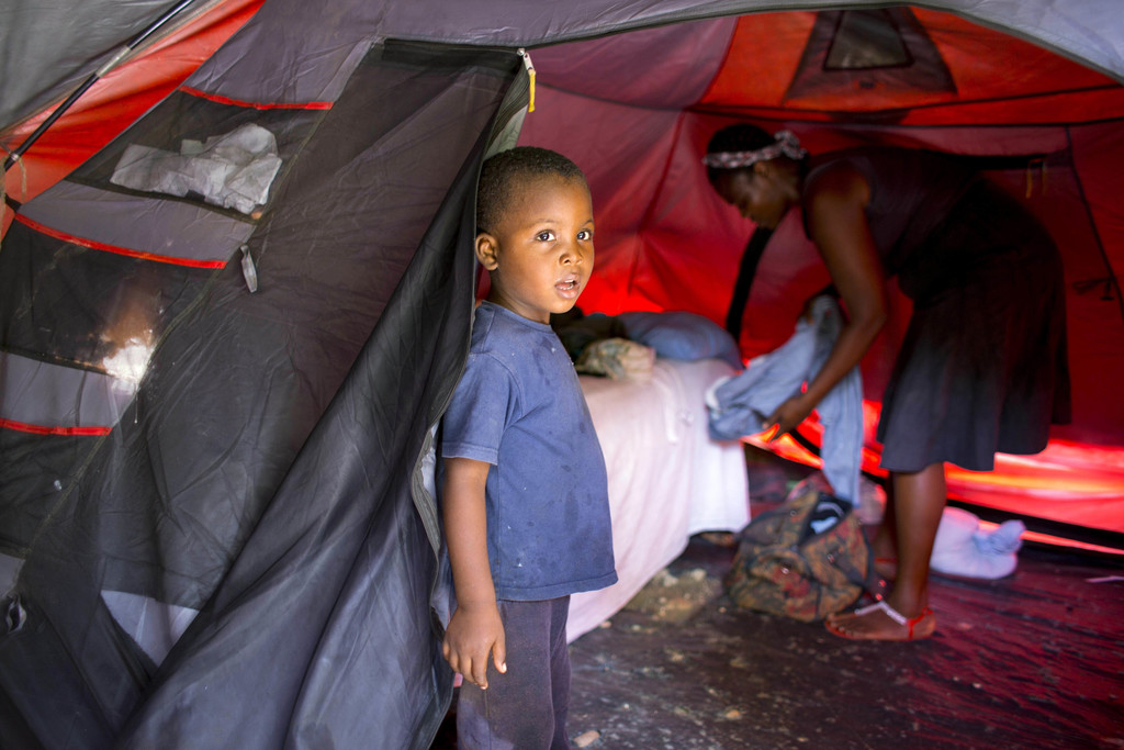 In this Aug. 15, 2016 photo, Marlene Andre 38, background right, arranges clothes while her son, Johnsley, 5, stands in front of their ...
