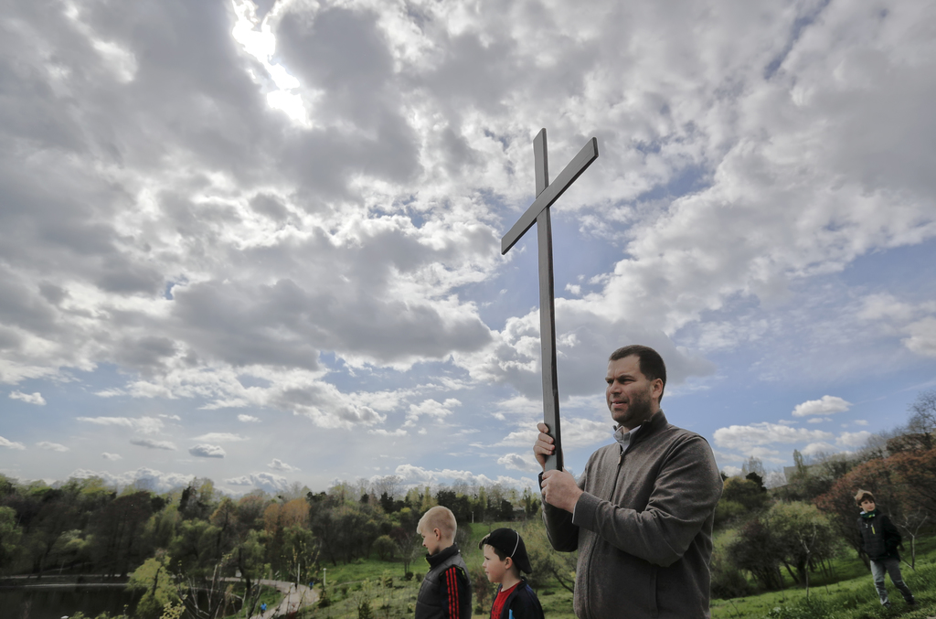 In this Saturday, April 8, 2017, picture a Romanian Catholic holds a wooden cross during a procession ahead of Palm Sunday in Bucharest...