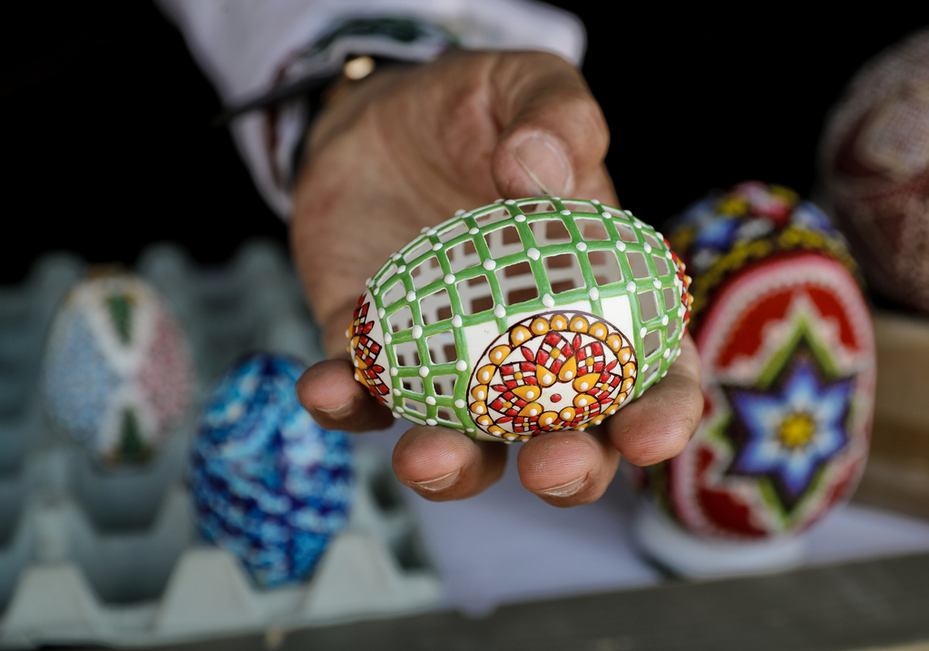 In this Thursday, April 13, 2017, picture artisan Nicu Poenariu displays for a photograph an Easter egg on sale at a fair in Bucharest,...