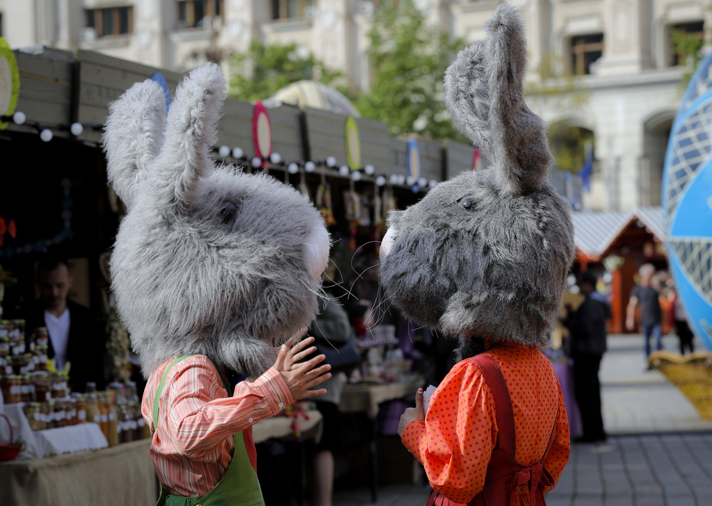 In this Thursday, April 13, 2017, picture entertainers wearing rabbit costumes speak at a fair in Bucharest, Romania. Ahead of Easter, ...