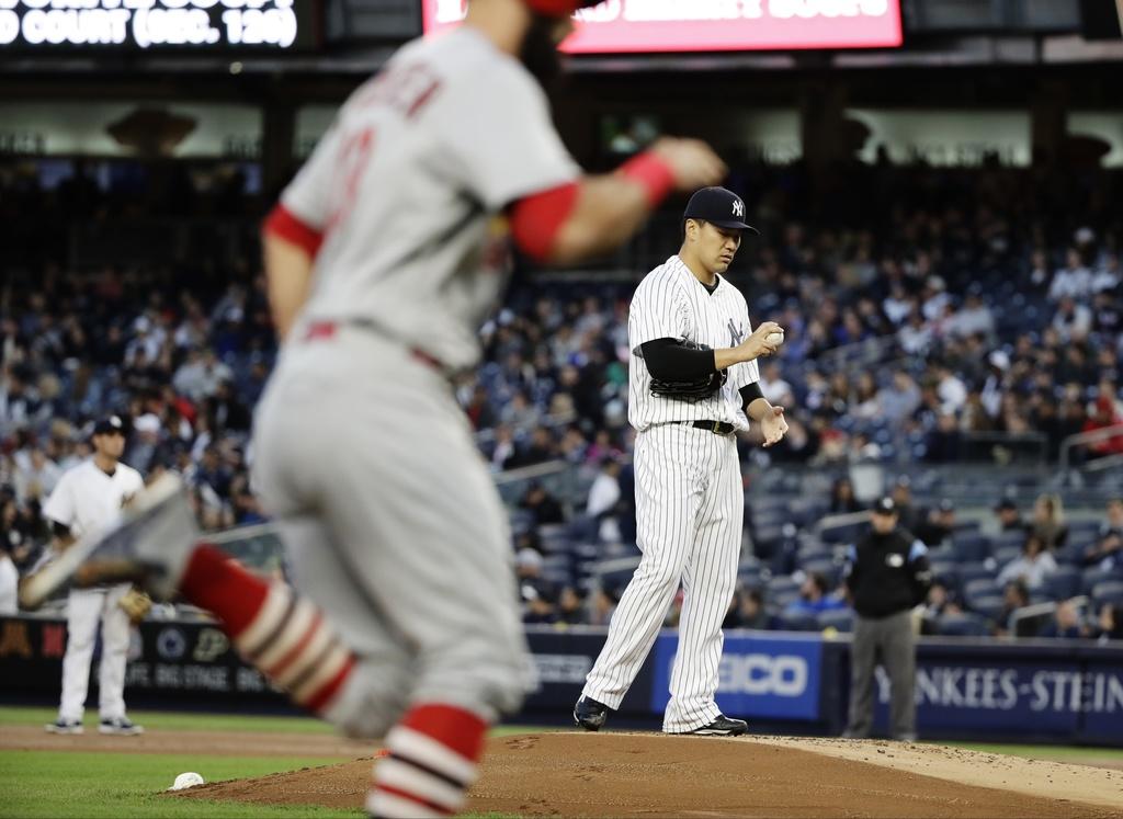 New York Yankees starting pitcher Masahiro Tanaka, right, of Japan, reacts as St. Louis Cardinals' Matt Carpenter, left, heads toward h...