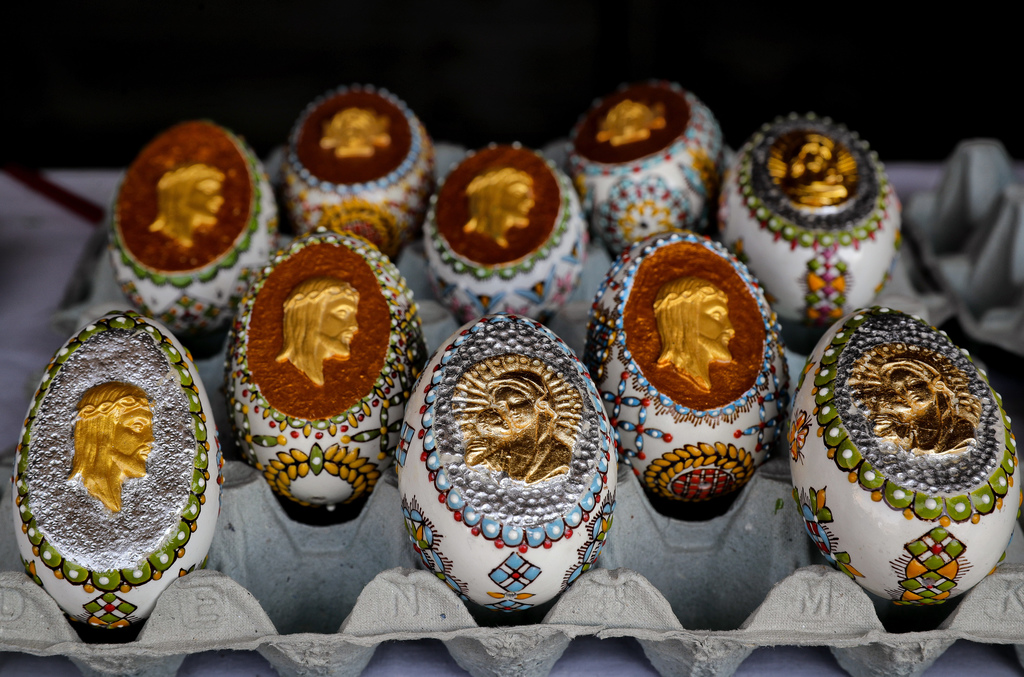 In this Thursday, April 13, 2017, picture Easter eggs decorated with religious themes by artisan Nicu Poenariu are on sale at a fair in...