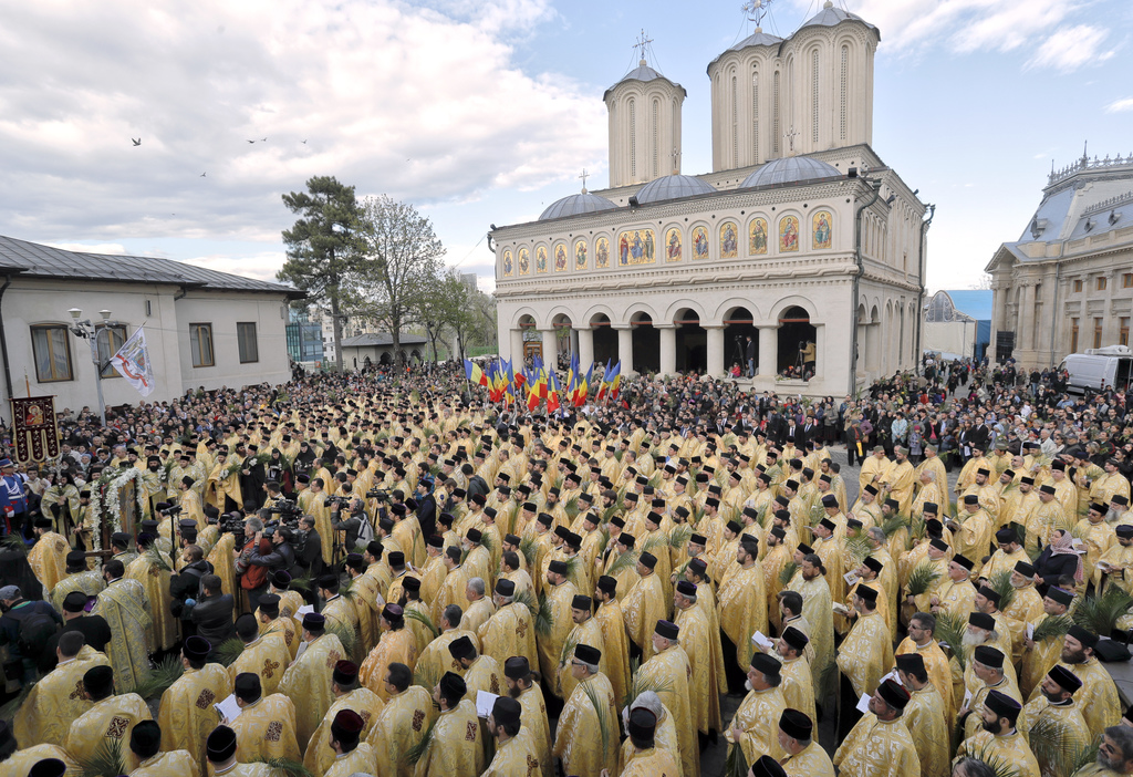In this Saturday, April 8, 2017, picture Romanian Orthodox priests attend a service ahead of Palm Sunday in Bucharest, Romania. Ahead o...