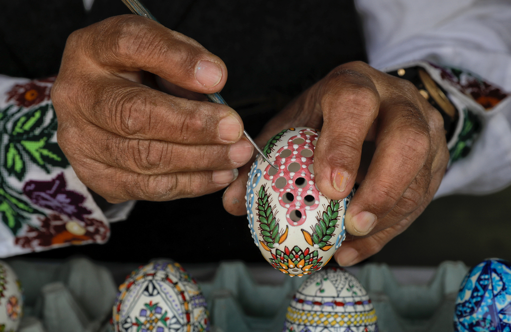 In this Thursday, April 13, 2017, picture artisan Nicu Poenariu demonstrates his technique on an Easter egg on sale at a fair in Buchar...