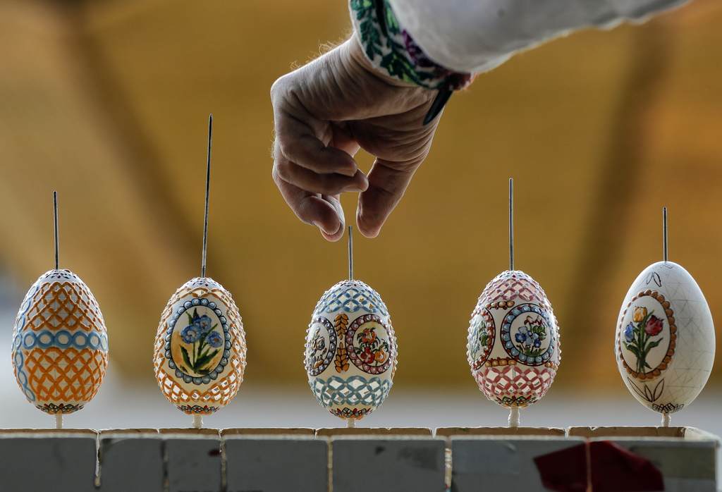 In this Thursday, April 13, 2017, picture artisan Nicu Poenariu turns Easter eggs on sale at a fair in Bucharest, Romania. Ahead of Eas...