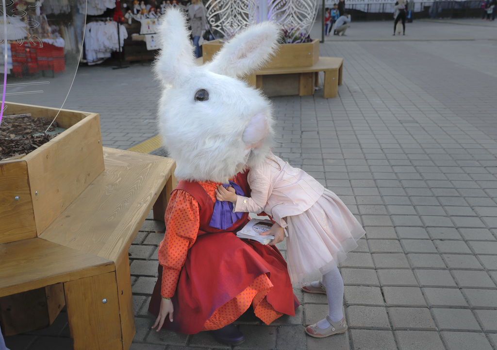 In this Thursday, April 13, 2017, picture a child hugs an entertainers wearing a rabbit costume at an Easter fair in Bucharest, Romania...