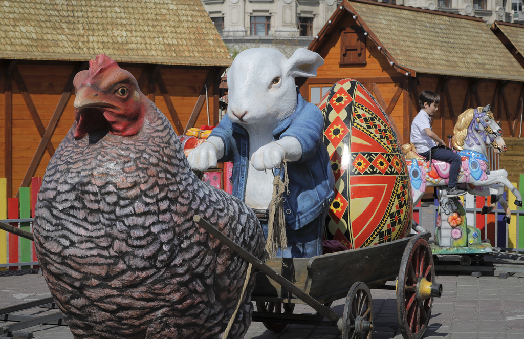 In this Thursday, April 13, 2017, picture a child enjoys a ride in an Easter inspired installation at a fair in Bucharest, Romania. Ahe...