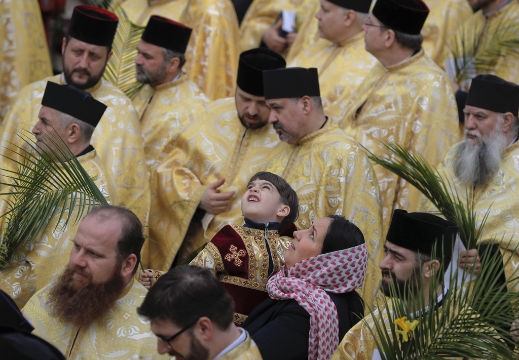 In this Saturday, April 8, 2017, picture a Romanian Orthodox priest's son looks up along with his mother during a service ahead of Palm...